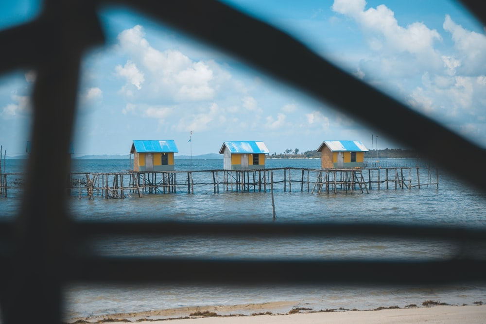 brown-white-and-blue nipa huts over body of water