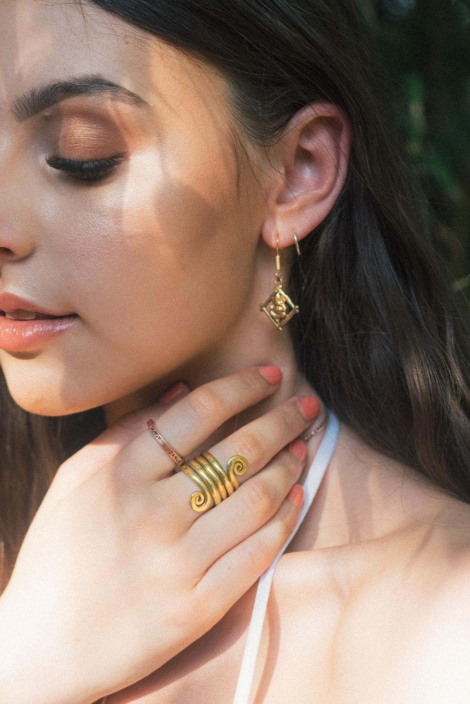 woman wearing gold-colored earrings