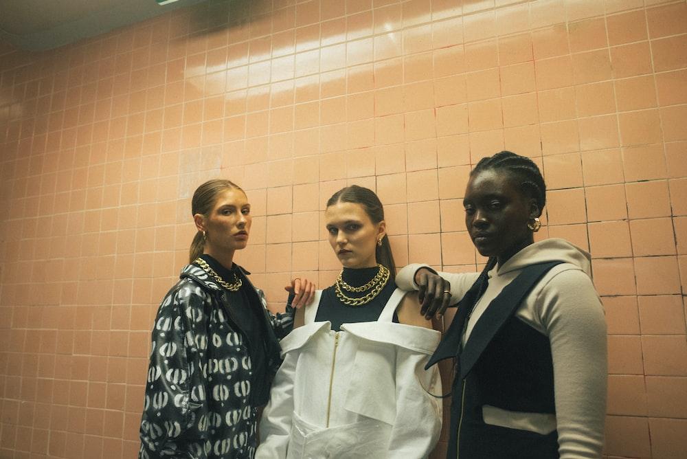 three women standing beside brown wall