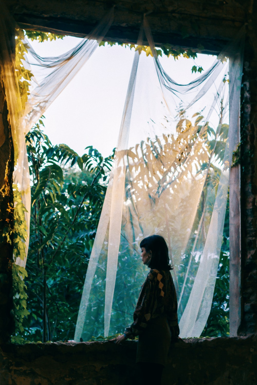 woman standing in front window with sheer curtain