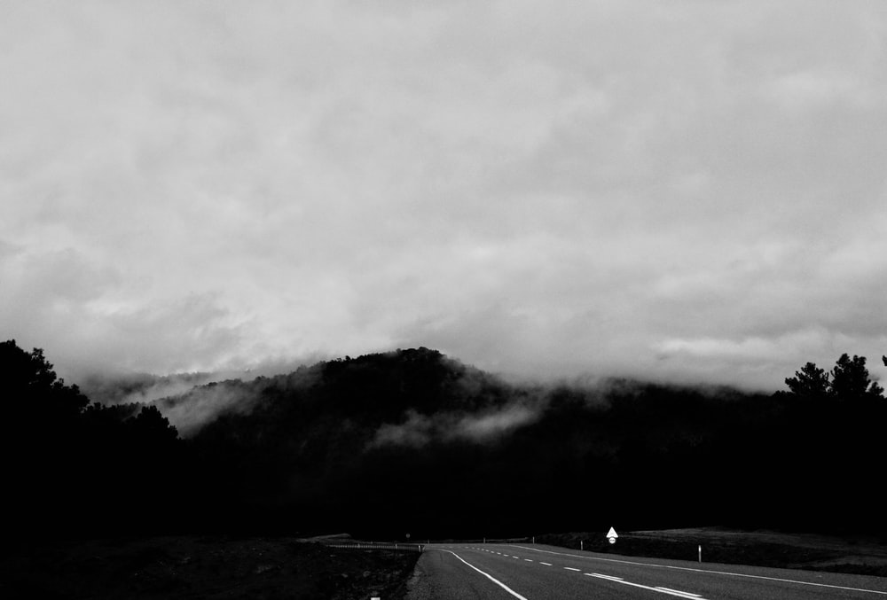 grayscale photography of roadway near mountain