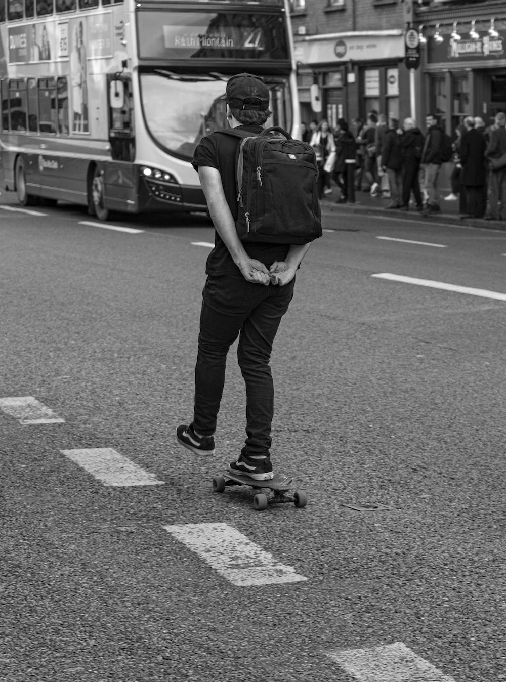 man skateboarding on road near bus in grayscale
