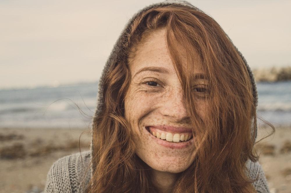 woman smiling wearing grey knit top