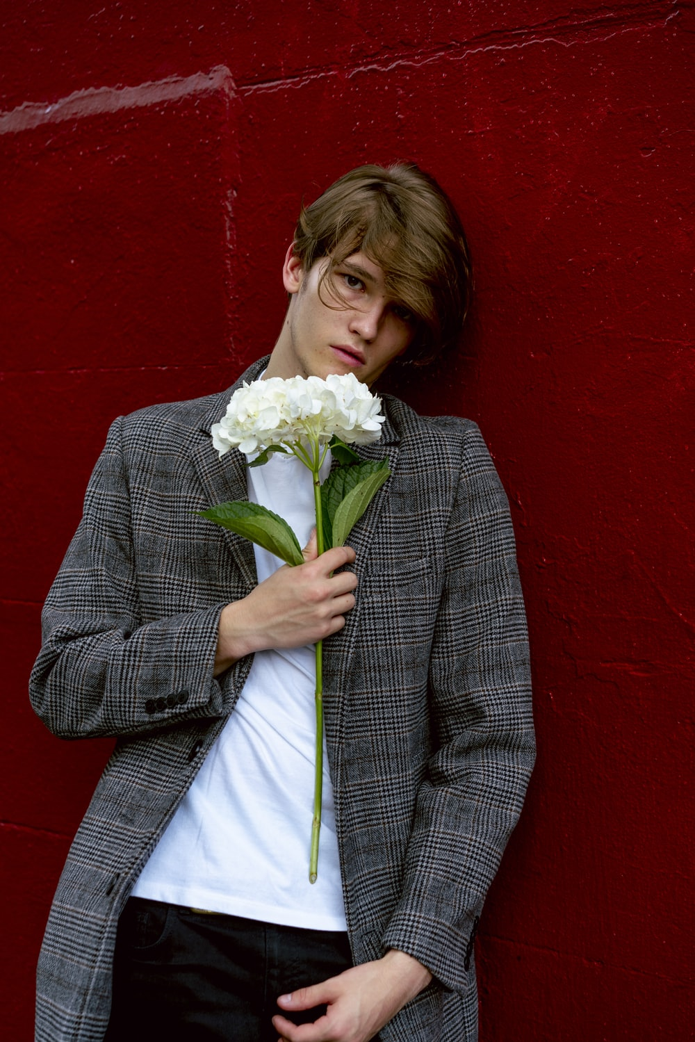 man wearing gray trench coat holding white flowers