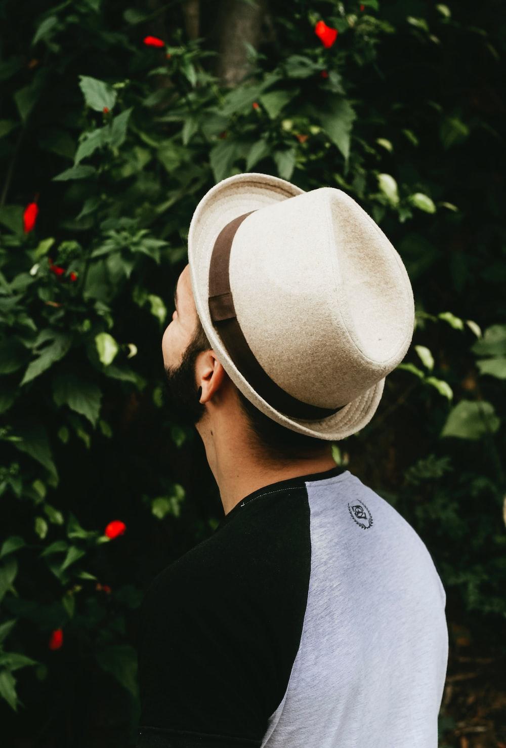man wearing black and grey shirt and grey fedora hat facing green bush