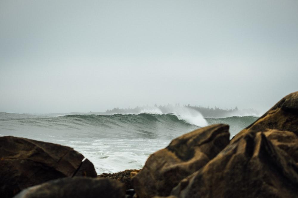 big ocean waves through rocks on shore