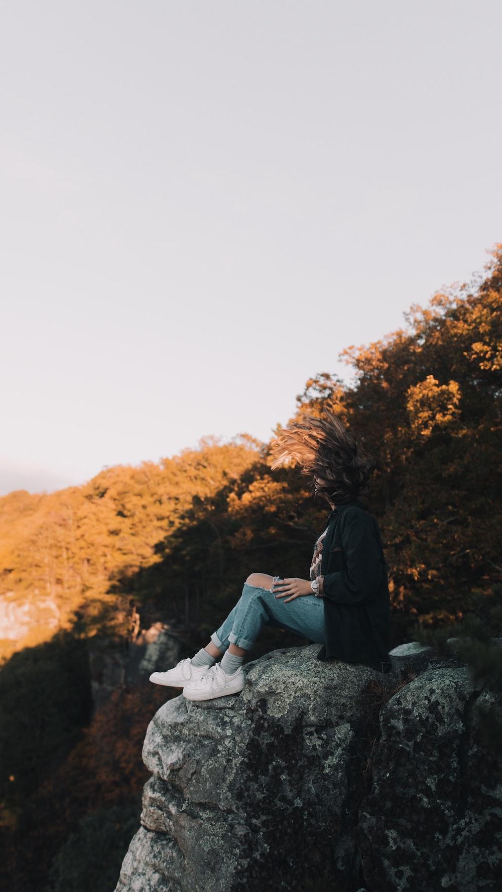 woman wearing black cardigan and blue denim jeans sitting on rock during daytime