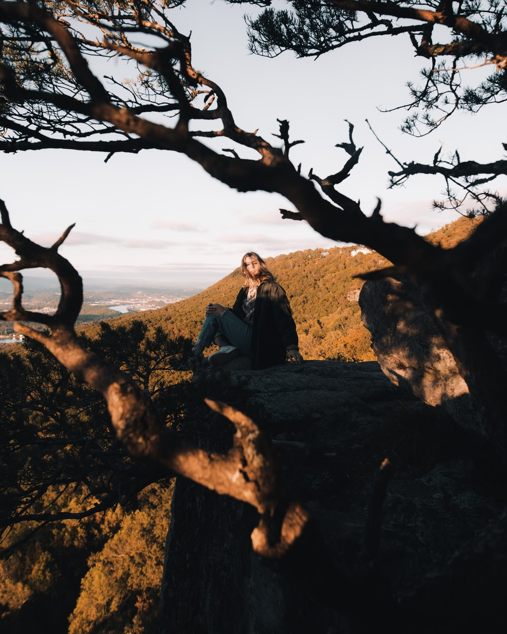 woman sitting on cliff near tree branches