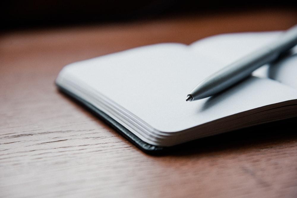 gray ballpoint pen on top of white book
