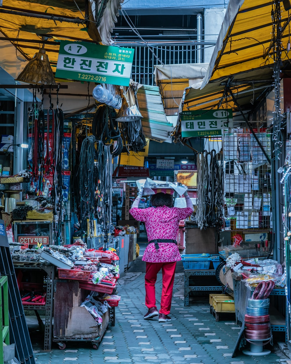 person in pink top walking beside stores