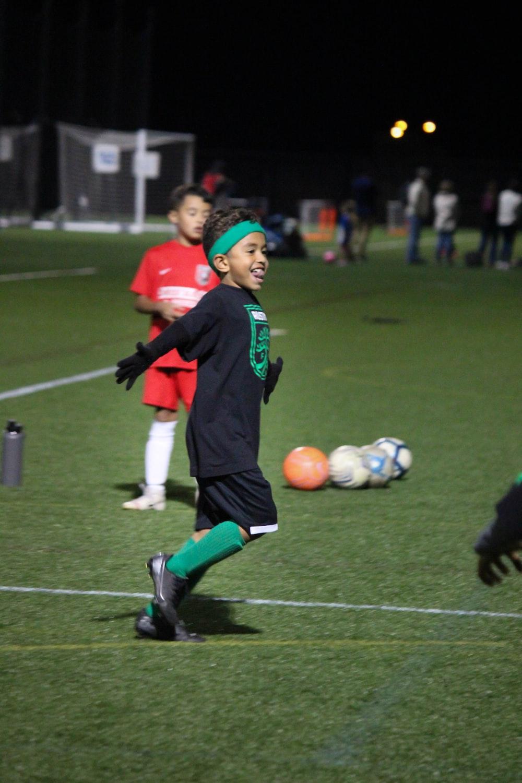 boy playing soccer on field