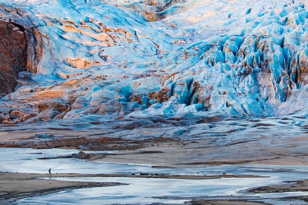 Man running under a huge glacier during sunrise