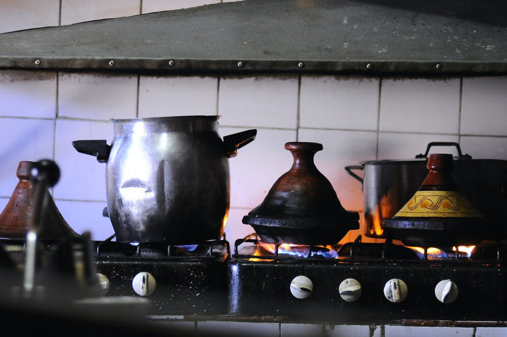 stainless steel cooking pot on black stove