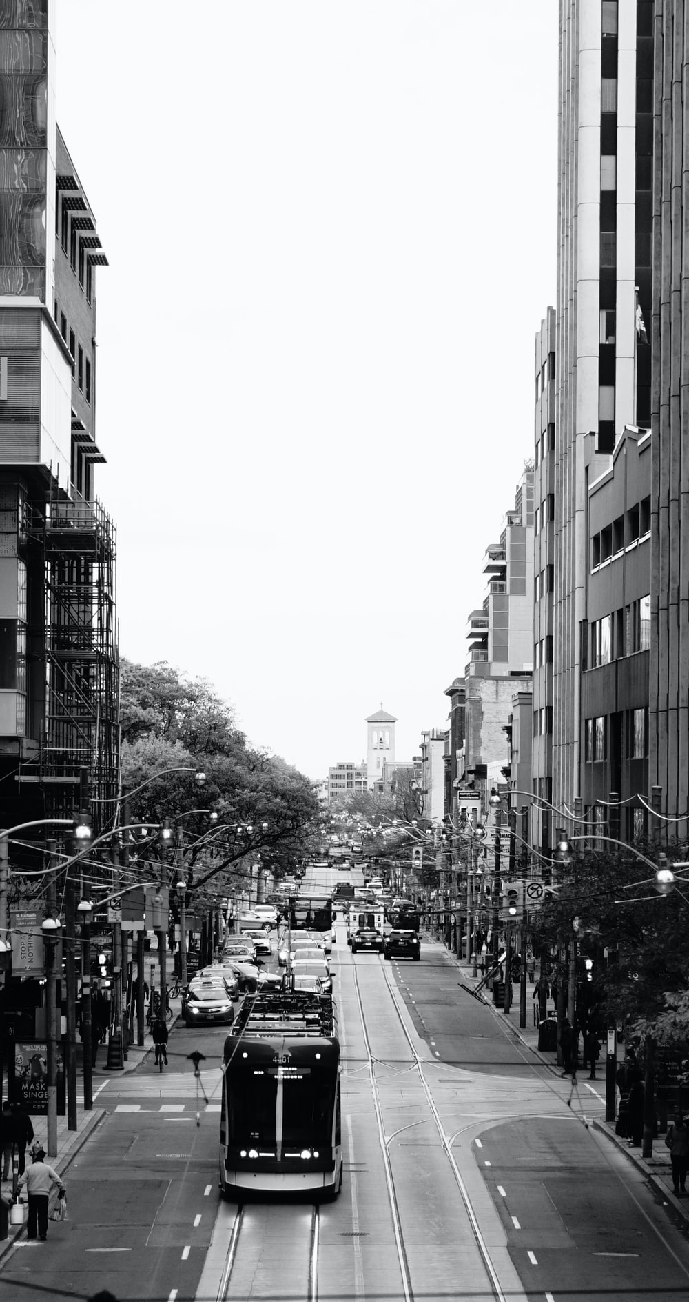 grayscale photography of a tram passing by city street