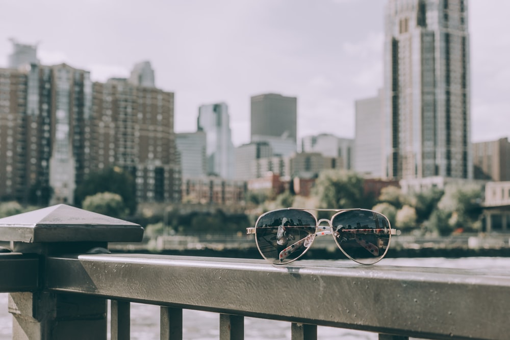 silver-framed Aviator-styled sunglasses on a metal railing