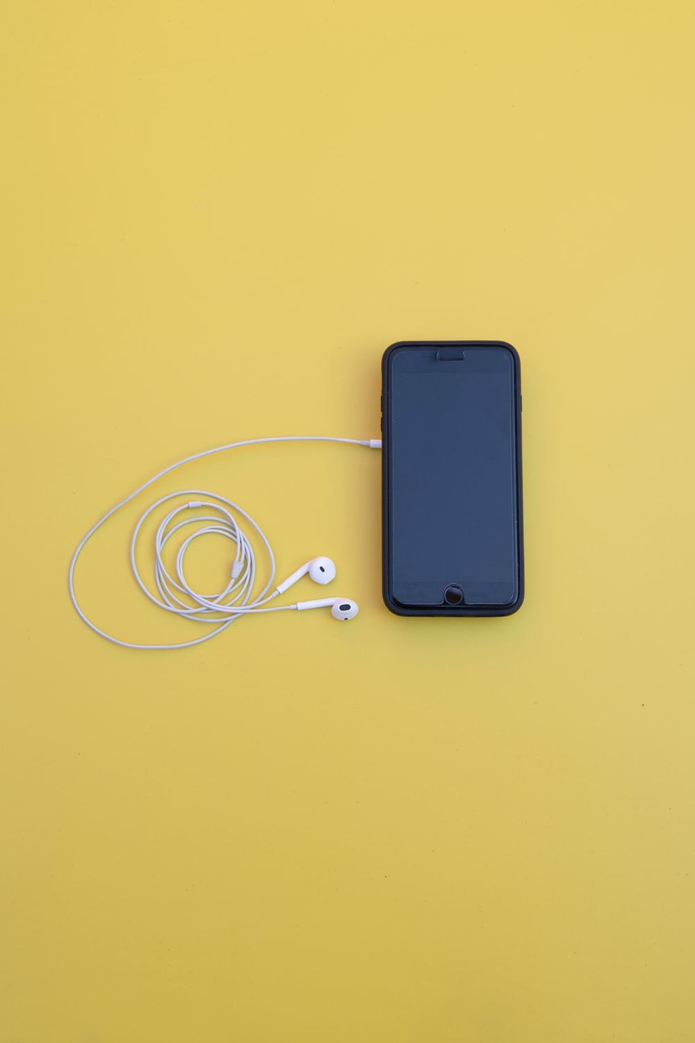 black iPhone X and white earpods