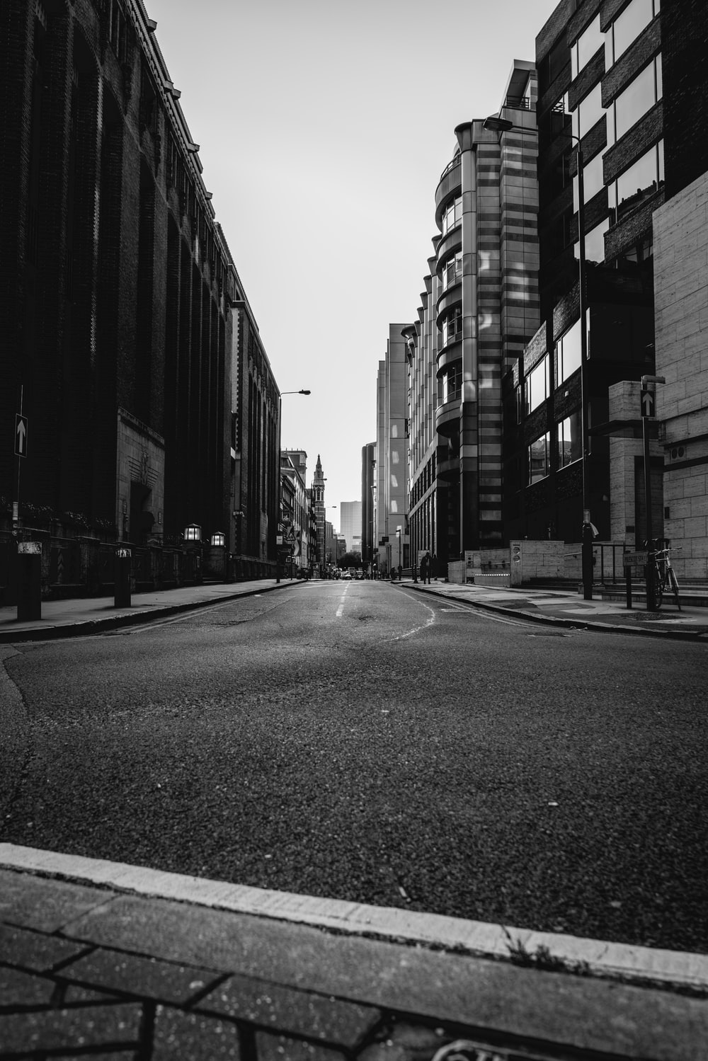 grayscale photography of a street between buildings
