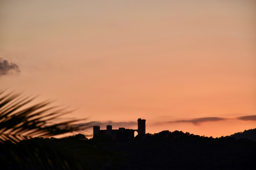 silhouette of castle during golden hour