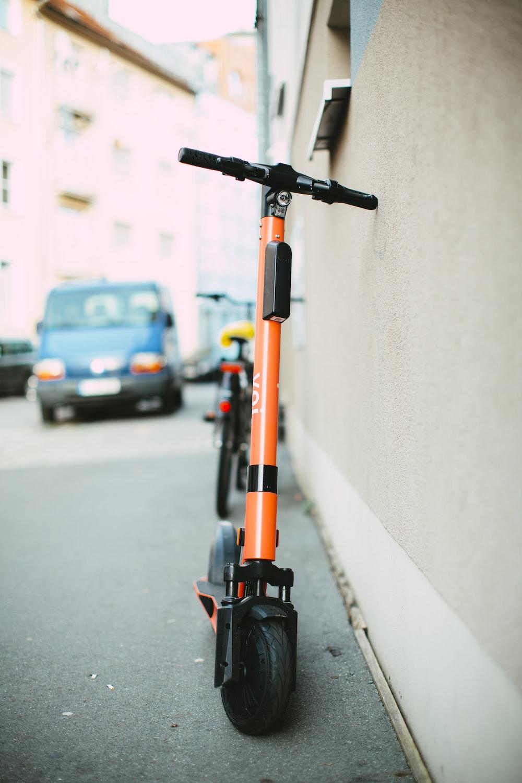 black and orange scooter parked on sidewalk