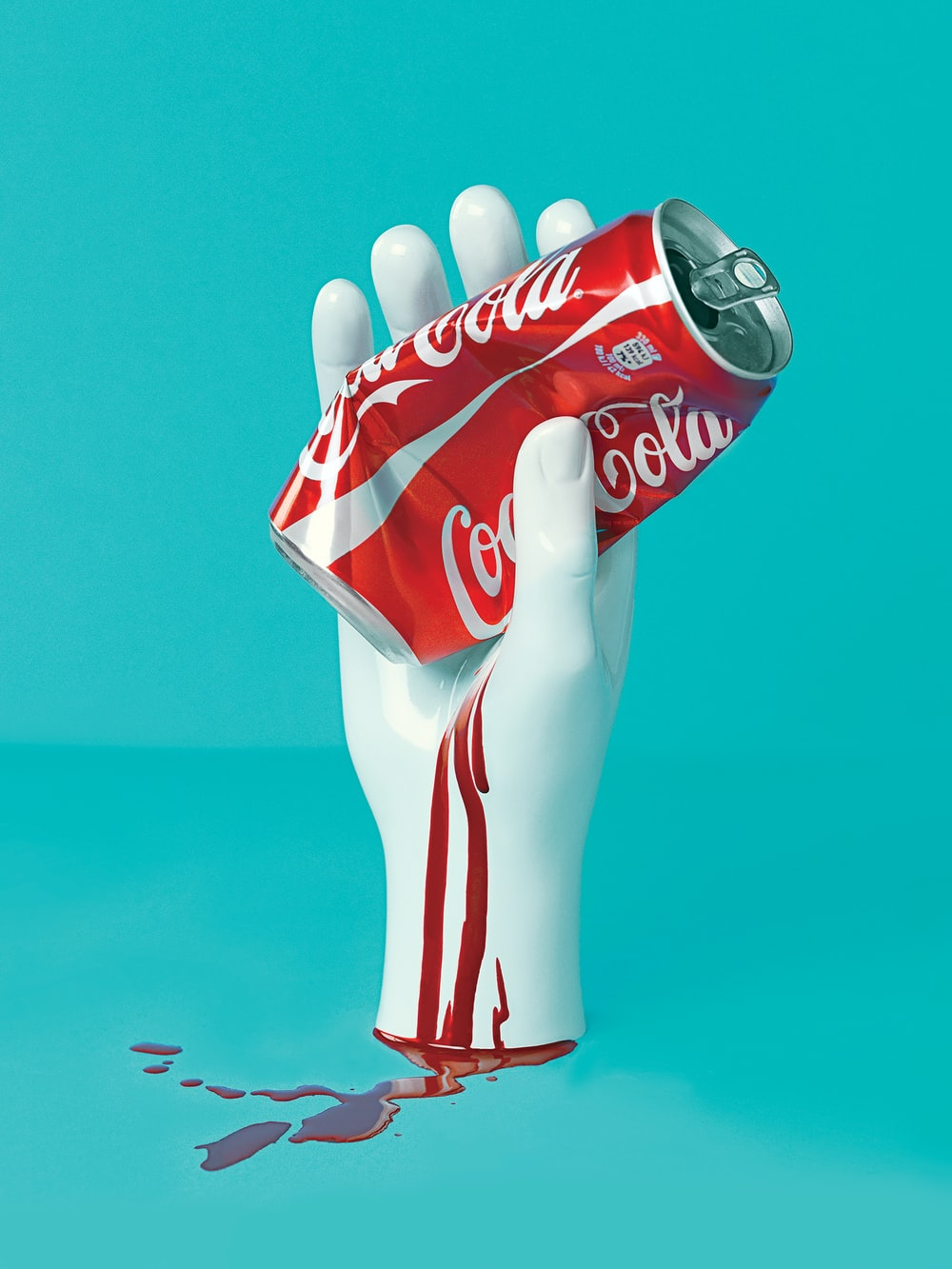 white hand holding Coca-Cola can statue