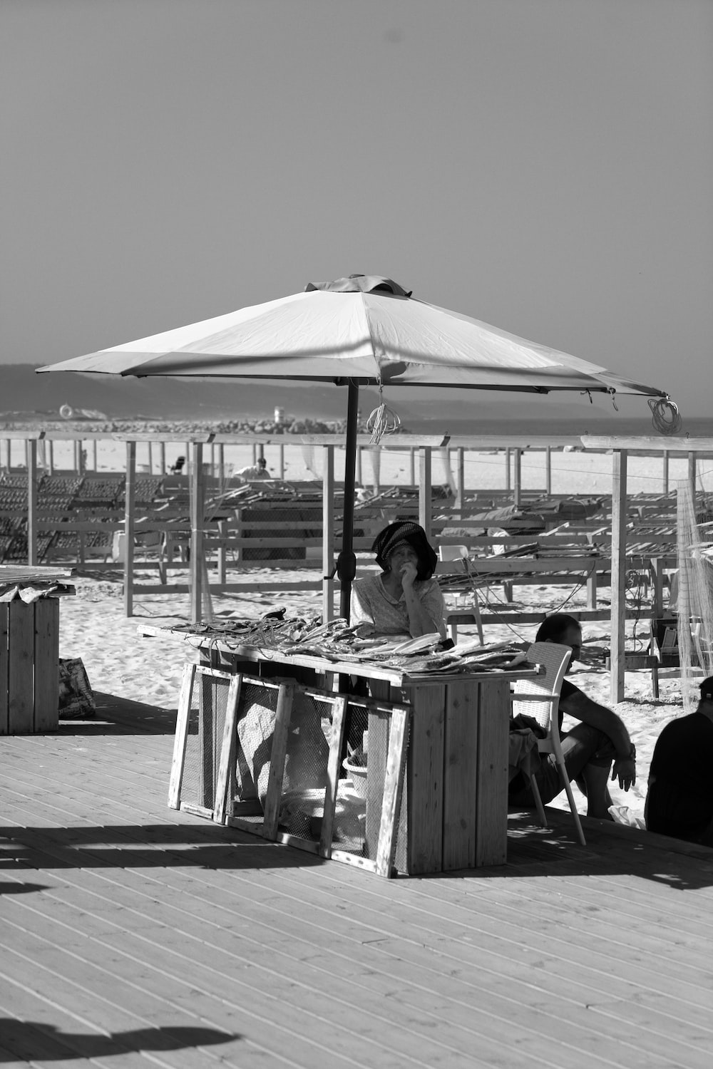 grayscale photography of woman sitting under a beach umbrella