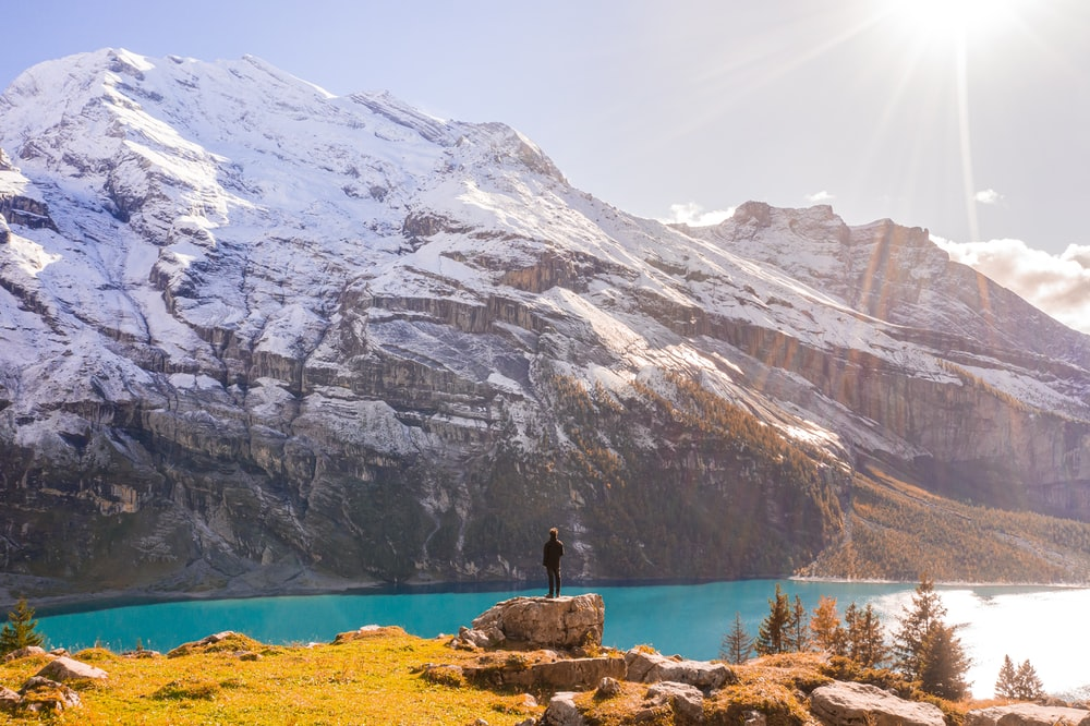 man at a rock by a lake and snowy mountains