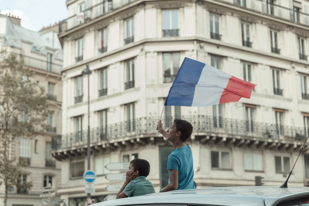 man in blue T-shirt holding flag of France