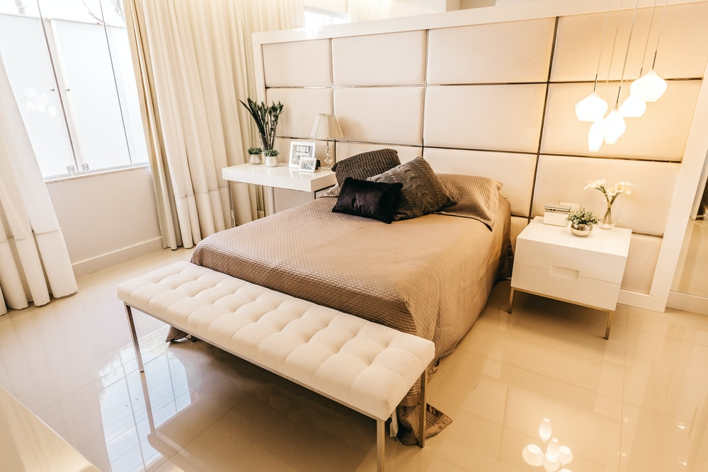 white nightstand and tufted white fabric bench beside bed