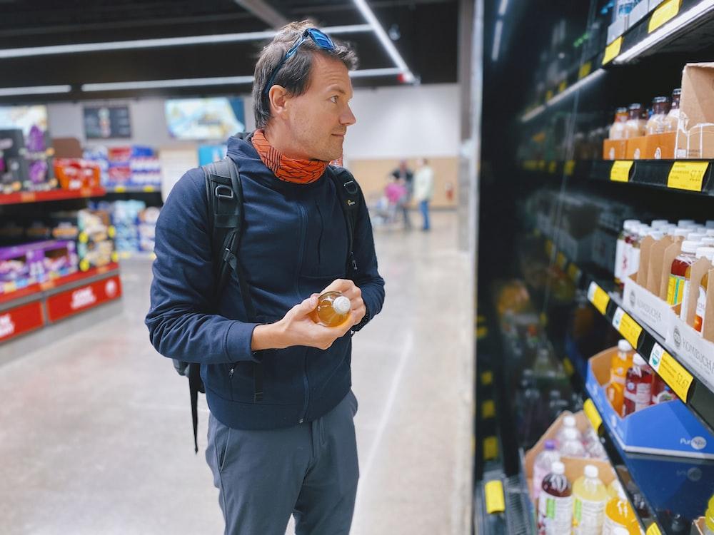 man standing beside display shelf