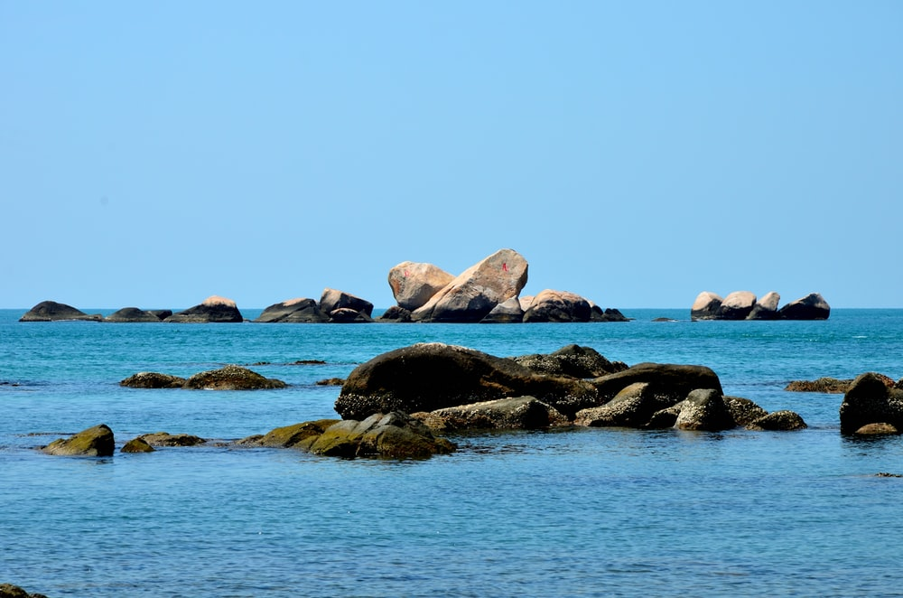 brown rocks surrounded by body of water
