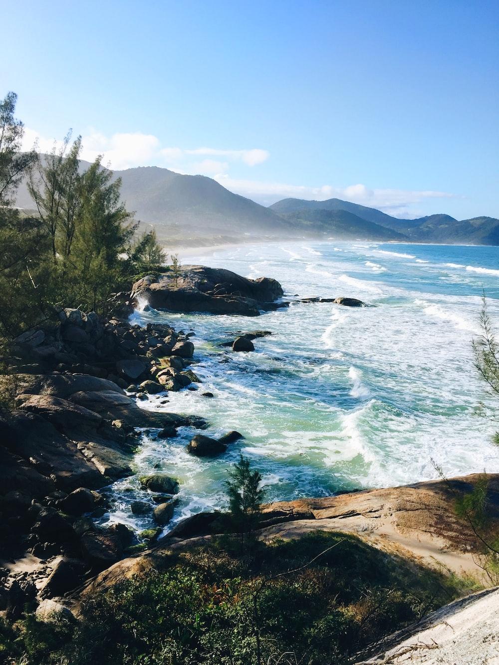 photo of seashore and mountain scenery