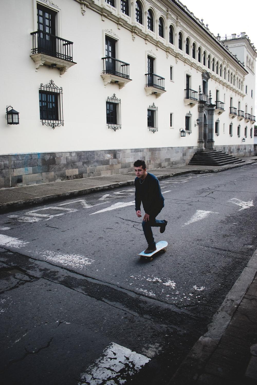 man wearing black long-sleeved shirt and black jeans riding skateboard