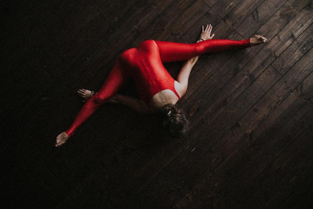 woman splitting and lying forward on parquet floor
