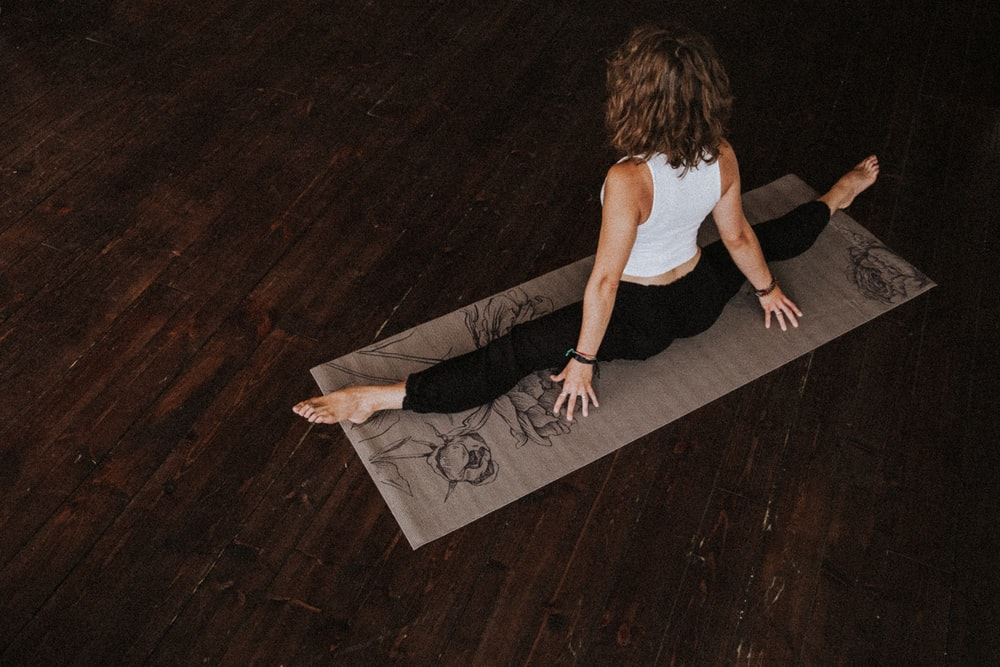 woman in white crop-top and black leggings doing yoga