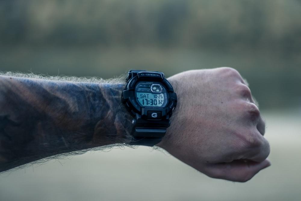 person wearing black round digital watch
