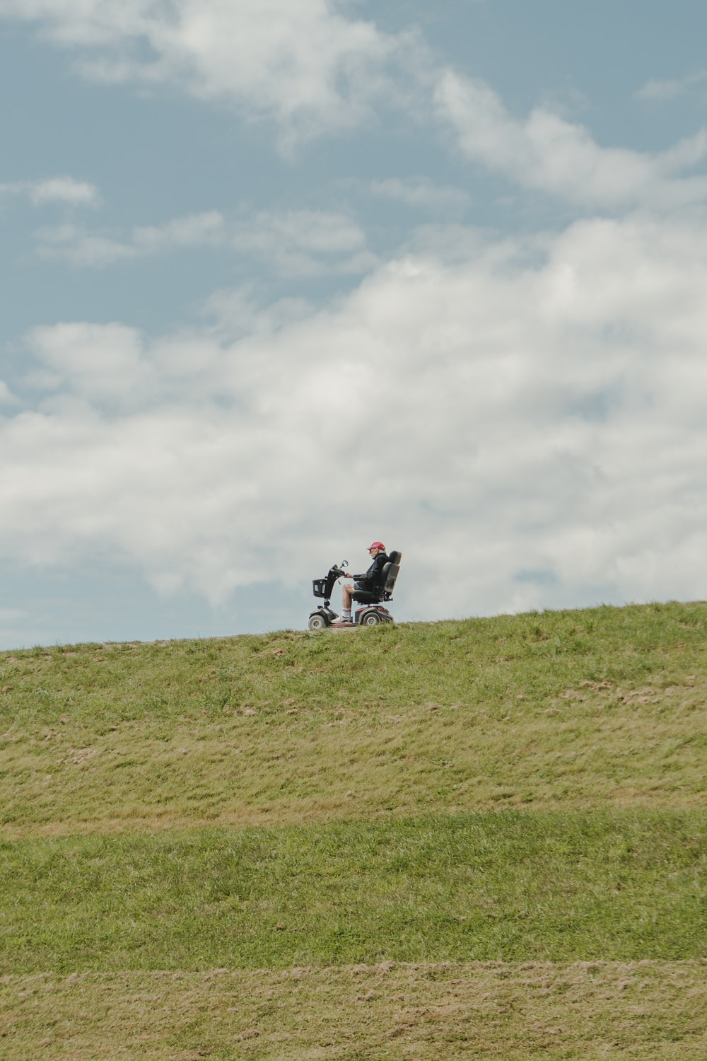 person sitting on mobility scooter during daytime