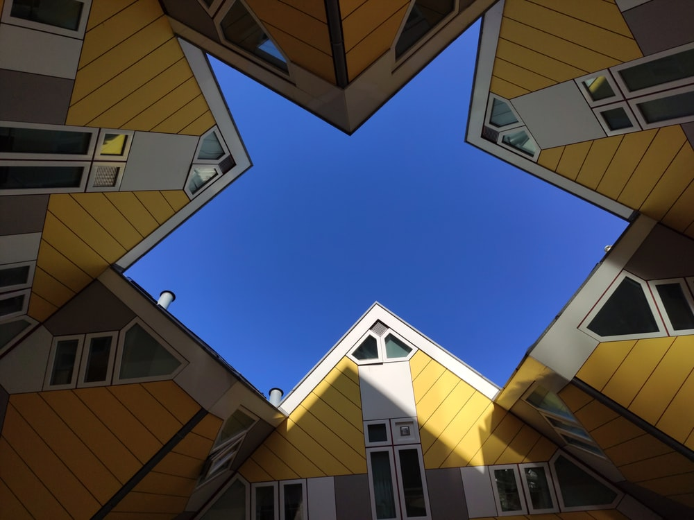 low-angle photography of yellow-and-gray houses during daytime