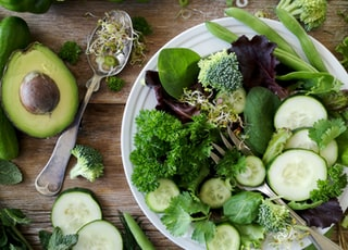 sliced broccoli and cucumber on plate with gray stainless steel fork near green bell pepper, snowpea, and avocado fruit