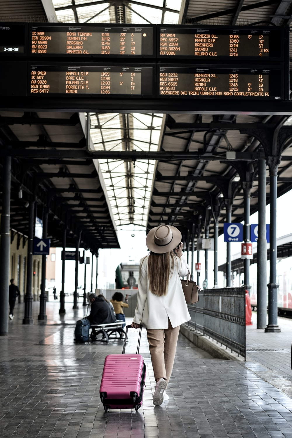 woman holding pink luggage