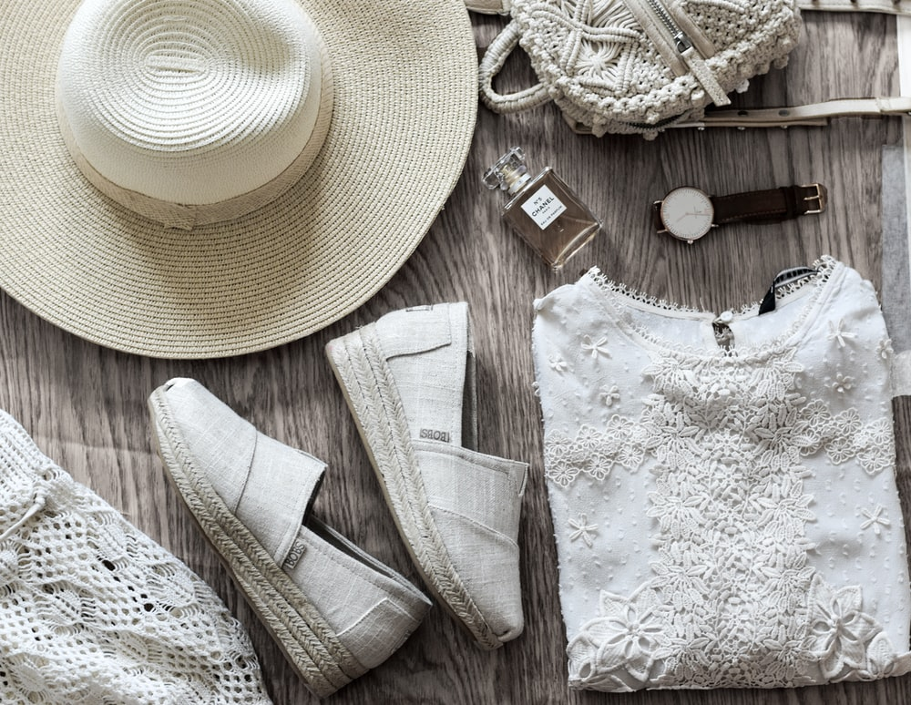 women's white shirt beside brown hat and pair of white sneakers