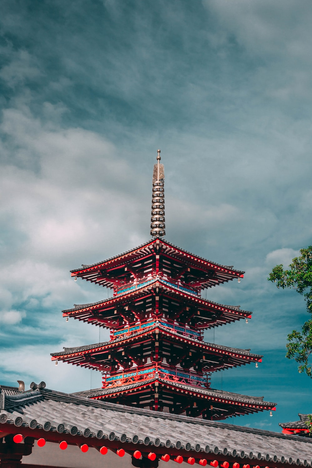 red and blue pagoda under a cloudy sky