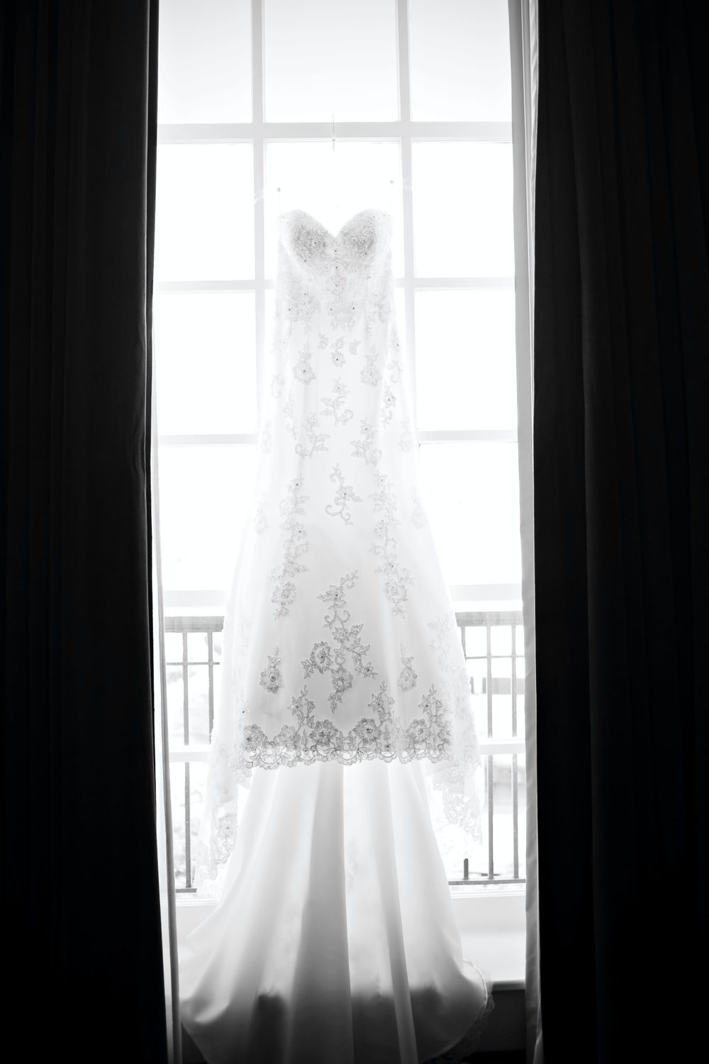 white floral wedding gown beside window