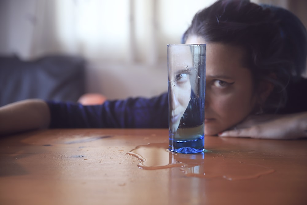 woman's reflection on blue glass cup