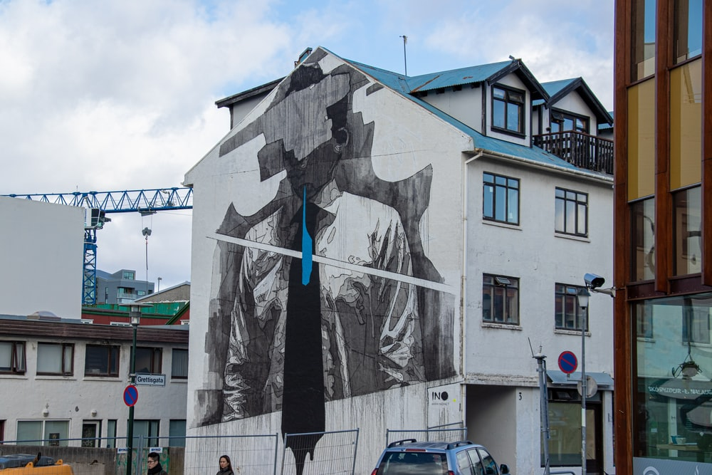man wearing shirt and necktie mural on building near buildings during day