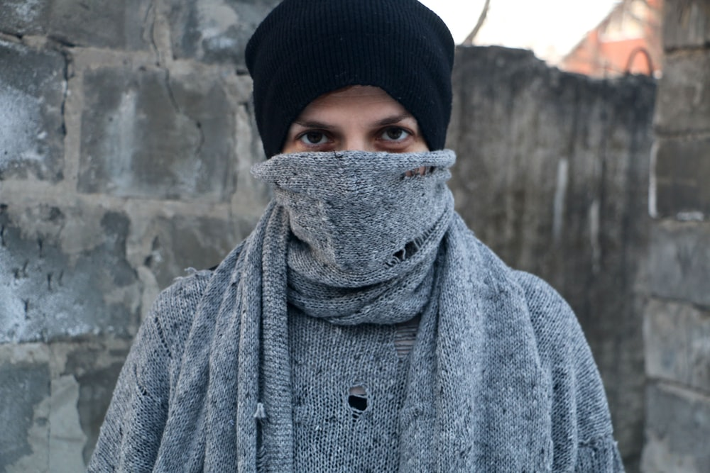 man covered his face by gray scarf