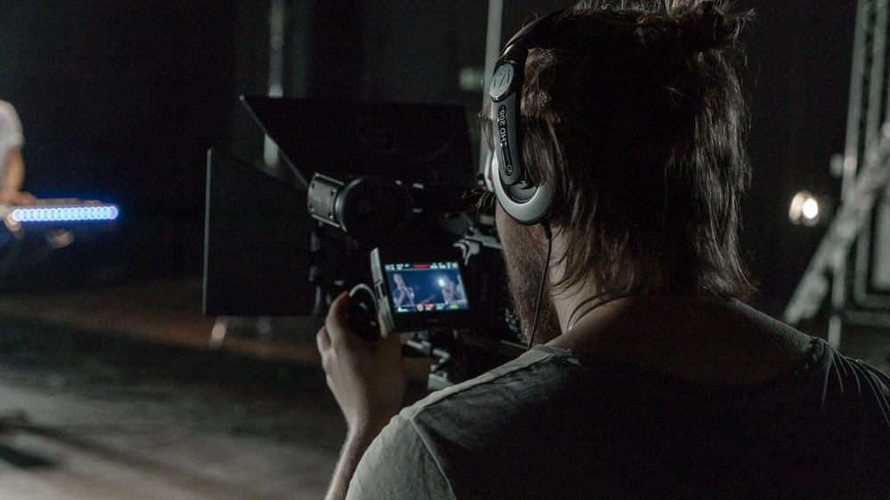 man in gray shirt holding camera