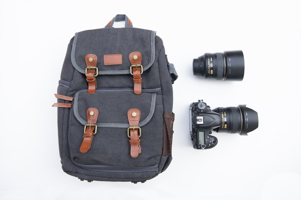 gray and black backpack near black DSLR camera and zoom lens