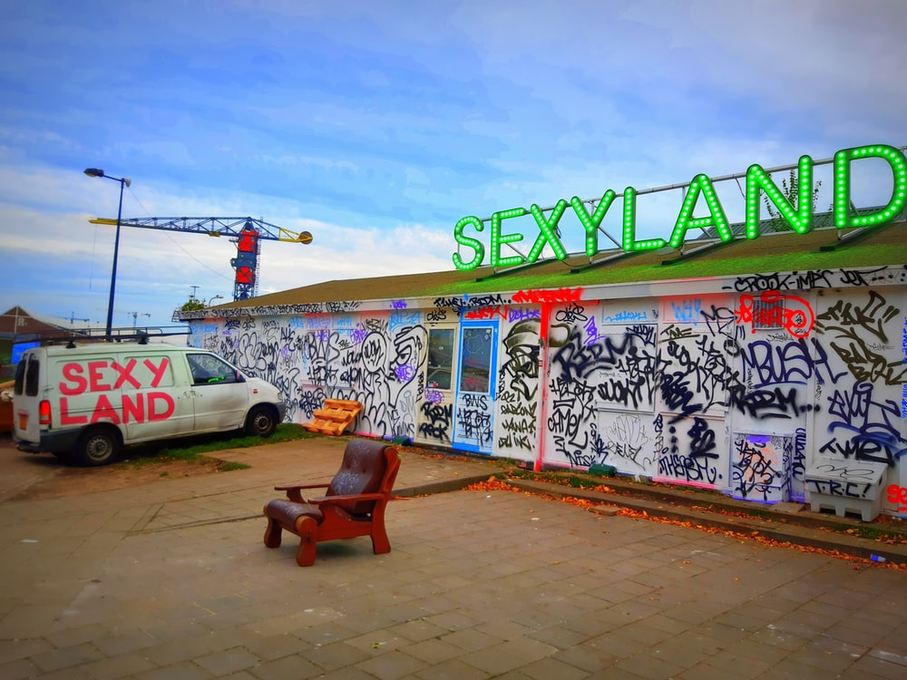 white van parked near Sexy Land building with signage