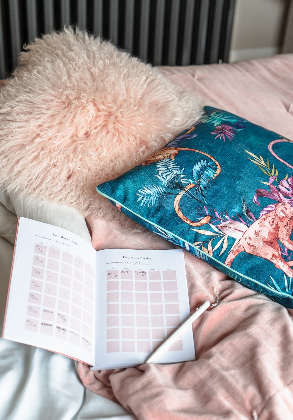 pen on top of a book beside throw pillows in bed