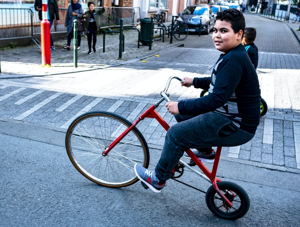 man wearing black and gray long-sleeved shirt and gray track pants riding red bike